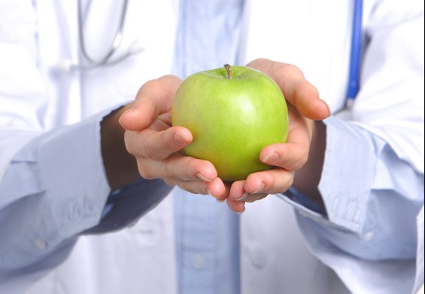 Naturopath holding an apple